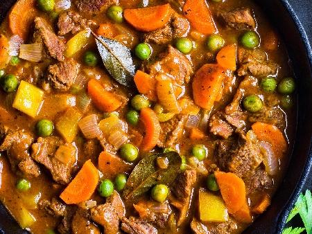 Лесна яхния със свинско месо, замразен грах, пресен зелен лук и домати в глинен гювеч или гювечета - снимка на рецептата